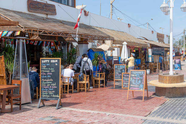 Restaurant on the pavement in Pisco, Peru People sitting on chairs outside a restaurant in Pisco, Peru. Seen during sunny day in the summer. pisco peru stock pictures, royalty-free photos & images