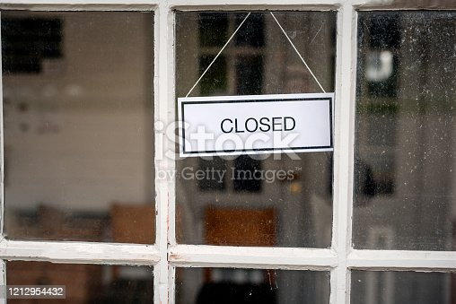 "A concept to illustrate the economic impact of the Covid-19 virus on the restaurant and catering business. Restaurant owner wearing his chef's whites changes the sign on his restaurant from ""Open"" to ""Closed"". Photographed on location in a restaurant on the island of Møn in Denmark."