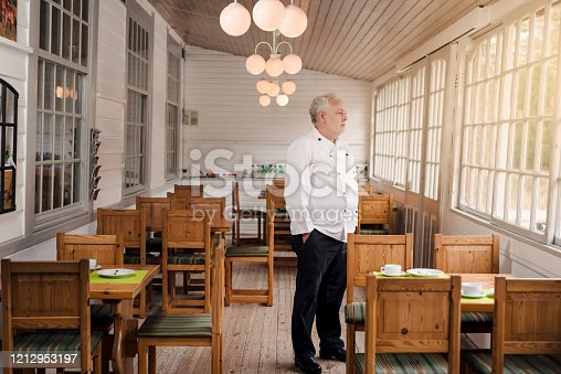 istock Restaurant owner standing in his empty restaurant. 1212953197