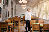 A concept to illustrate the economic impact of the Covid-19 virus on the restaurant and catering business. Restaurant owner wearing his chef's whites standing in his empty restaurant. Photographed on location in a restaurant on the island of Møn in Denmark.