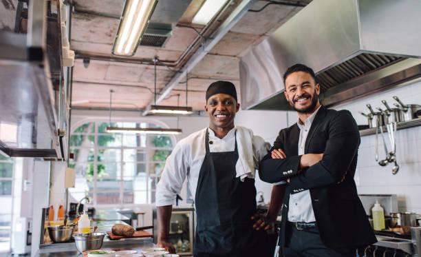 propietario del restaurante con chef en cocina - restaurante fotografías e imágenes de stock