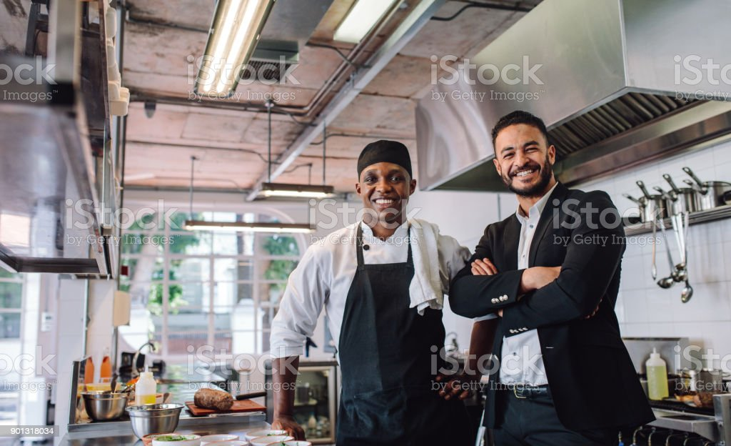 Restaurant owner with chef in kitchen stock photo
