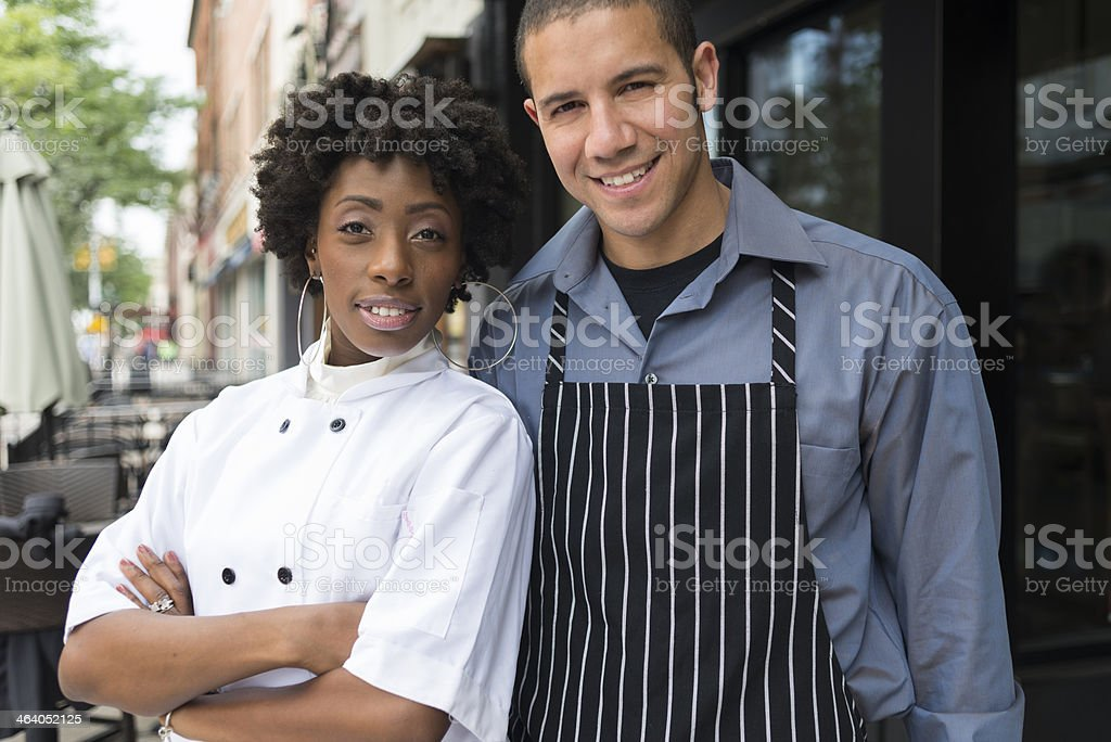 Restaurant owners posing in front of the restaurant stock photo