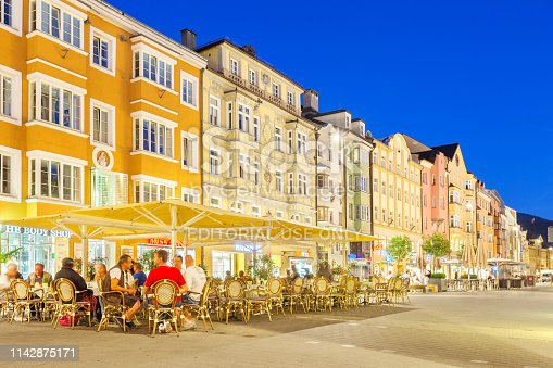 People have dinner at a restaurant patio on Maria Theresien Strasse in downtown Innsbruck, Austria in the evening.