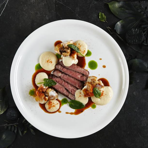 Restaurant Plate von schwarzem Angus Beef Filet mit warmen Kartoffeln in Käse-Sauce und Pilz Espuma – Foto