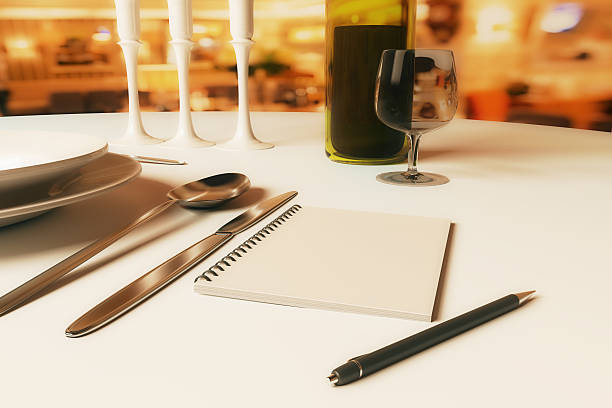 Restaurant rating and criticism concept Close up of dining table with blank spiral notepad, candles, wine, cutlery and other items. Restaurant rating and criticism concept. 3D Rendering critic stock pictures, royalty-free photos & images