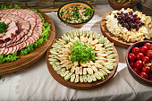 Restaurant table full of different appetizers: tapas rolls with vegetables, bowl with marinated tomatoes, meat assortment, cheese assortment with fresh grape and marinated mushrooms.