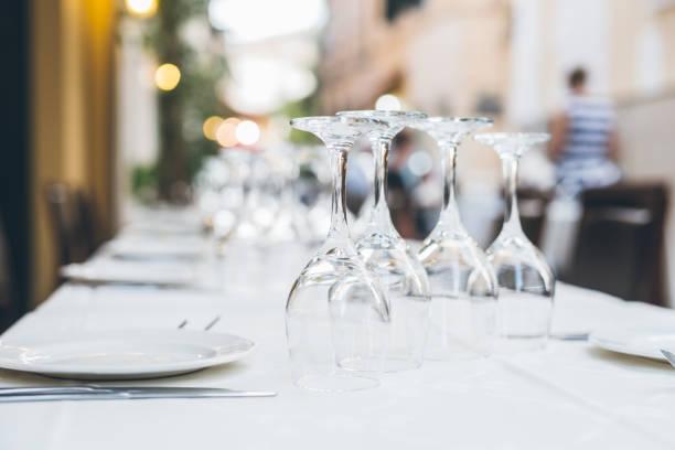 restauranttisch mit geschirr und wein gläser - griechische partyspeisen stock-fotos und bilder