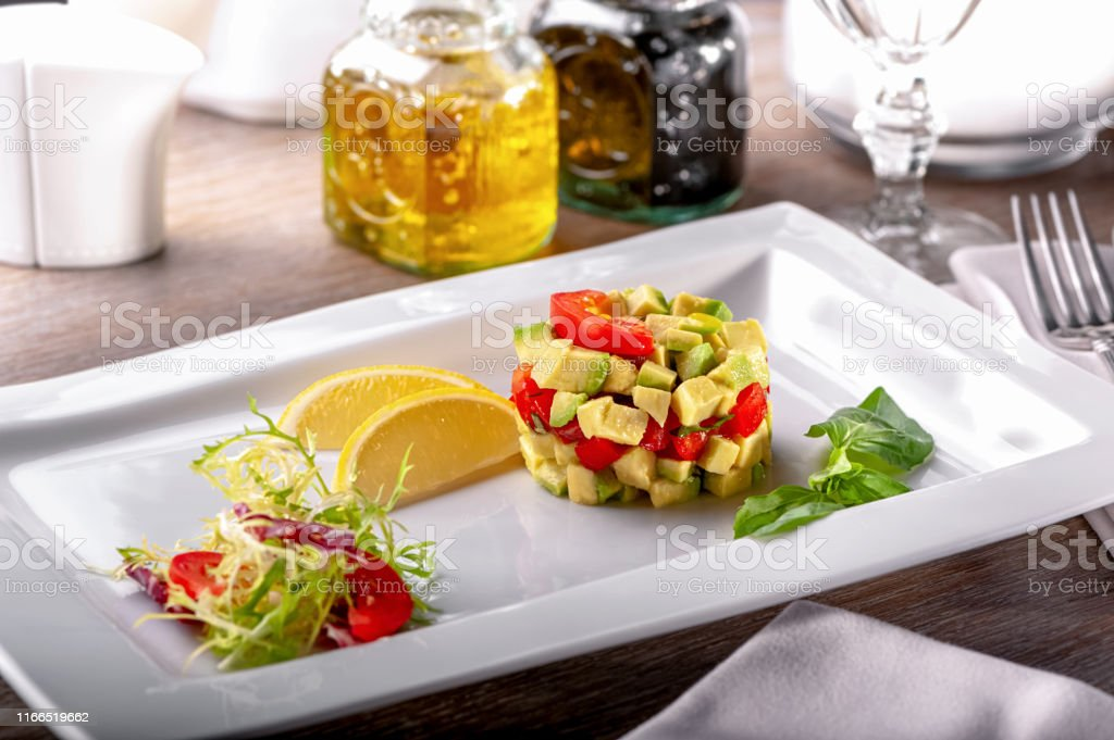restaurant table with dish of cold appetizers tomato and avocado...