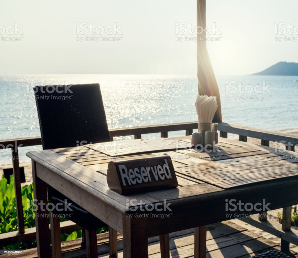 Restaurant table, with reserved sign at beach sea view stock photo
