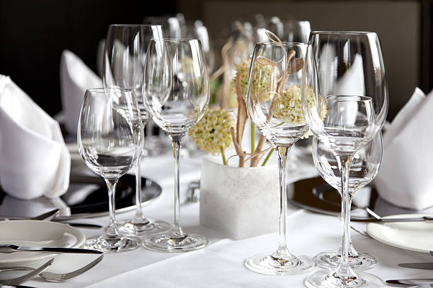 Restaurant table with wine glasses and napkins stock photo
