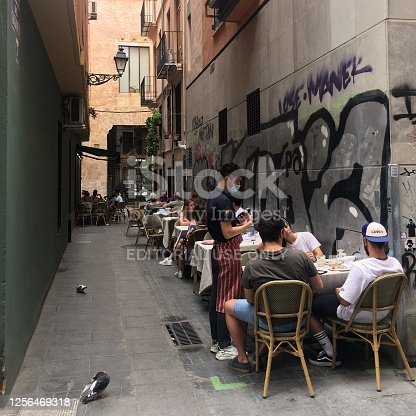 Valencia, Spain - July 12, 2020: Tables arranged in narrow street with people eating. This area is visited by lots of tourists and offers a lots of different places to eat and drink