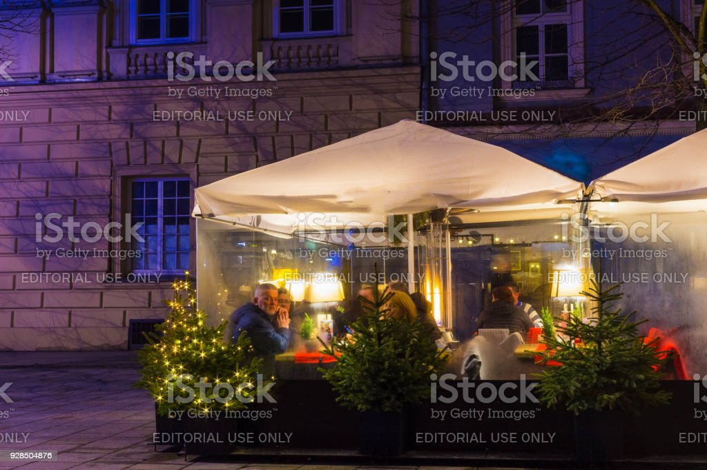 People resting at restaurant tables on main market square of Krakow...