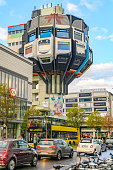 Berlin, Germany - October 5, 2019: Restaurant tower of the seventies from painted concrete in a business street in Berlin-Steglitz against blue sky.