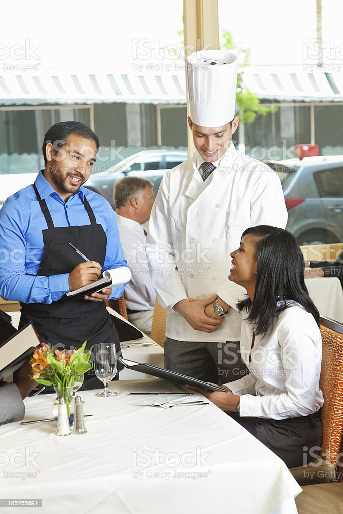 Restaurant waiter and chef making menu recommendations royalty-free stock photo