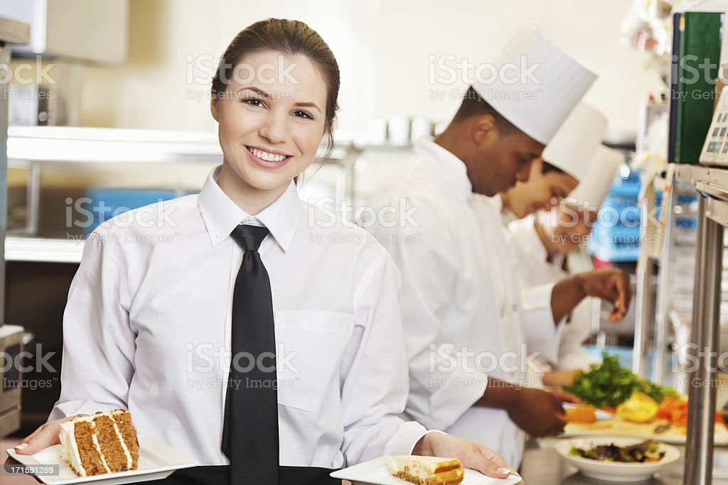 Restaurant waitress holding deserts prepared by professional chefs stock photo