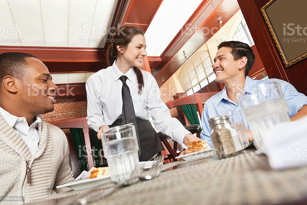 Restaurant waitress serving food to guests stock photo