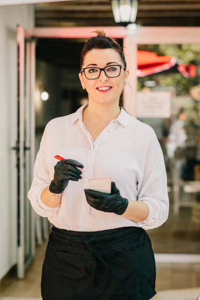Restaurant waitress taking note of order to customers.