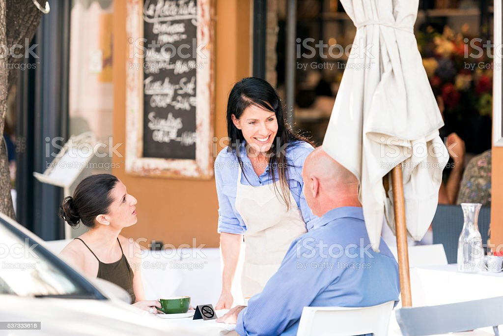 Restaurant Waitress Talking To Her Customers Smiling waitress chatting to an adult couple sitting at an outside restaurant table at daytime. Adult Stock Photo