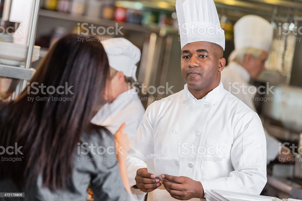 Restaurant waitress yelling at chef in kitchen with late tickets stock photo