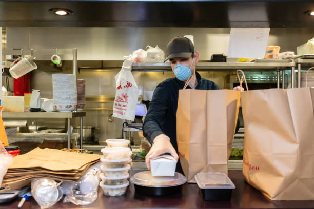 Restauranteur Wearing Mask and Gloves Packaging Food for Delivery During Covid-19 Outbreak