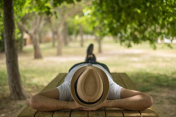 restful boy laying down on a park wearing a hat - een dutje doen stockfoto's en -beelden