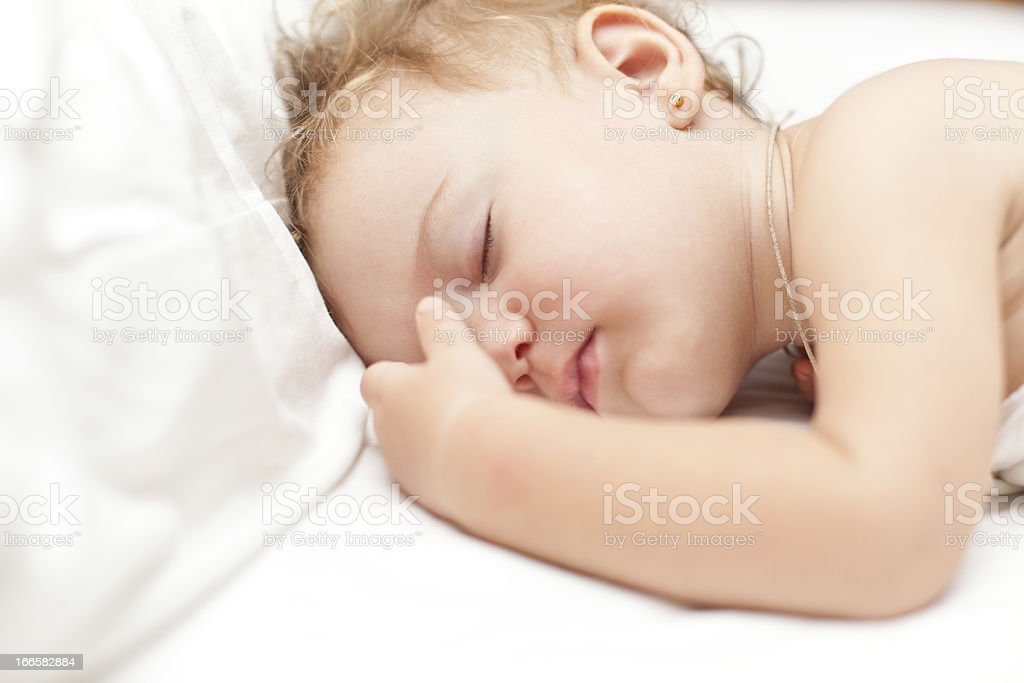 Restful two years old baby girl sleeping on bed stock photo