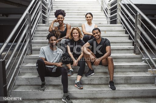 Multi ethnic group of young  people exercise outdoor. They are wearing sport clothing, sitting on stairs and posing for photo