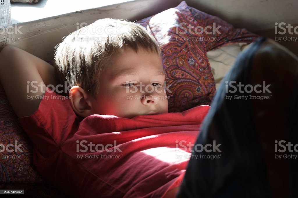 Resting and reading teenage boy wearing red t-shirt in backlit – Foto