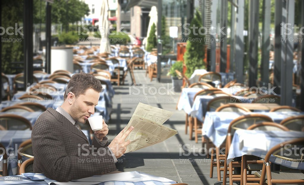 Resting businessman drinking coffee and reading newspaper in the - Royalty-free Adult Stock Photo