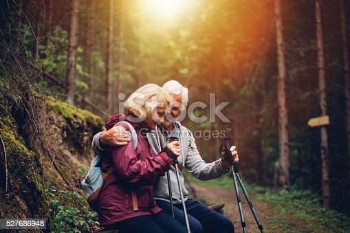 Photo of a senior couple, resting on the bench during the hike through the forest