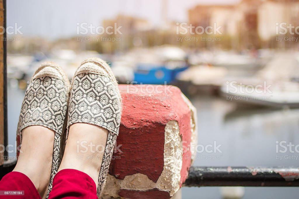 Resting female legs on the wall next to the sea stock photo