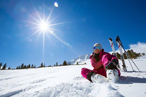 resting female skier in winter resort stock photo