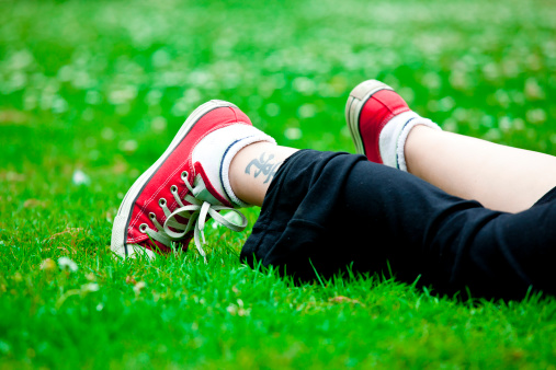 Resting on the grass.