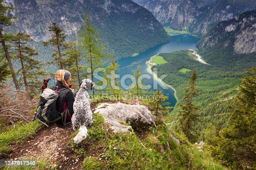 Germany, Bavaria, Berchtesgaden.  A young woman sits on a view point with heer dog near Lake Königssee.