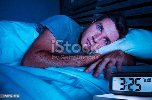 istock restless worried young attractive man awake at night lying on bed sleepless with eyes wide opened suffering insomnia sleeping disorder depressed and sad in rest privation stress concept 973262420