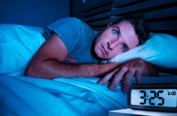 unruhig besorgt junge attraktive mann wach in der nacht auf bett schlaflos mit großen augen öffnete leiden schlaflosigkeit schlafstörungen deprimiert und traurig im rest entbehrung stress konzept - aufwachen stock-fotos und bilder