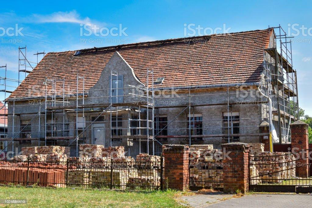 Restaurierung eines alten Bauernhauses. Im Garten sind neue Dachziegel für die Reparatur des Daches und die alten Ziegelsteine der Fassade. – Foto