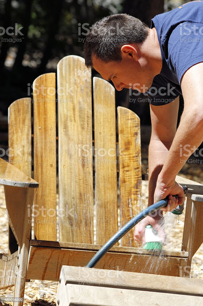 Restoration: Teak wood chair - man cleaning stock photo