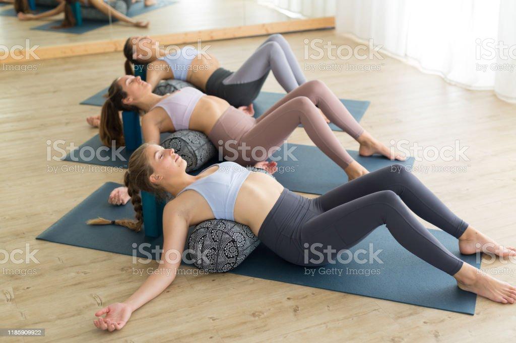 Restaurativeyoga mit einer Stütze. Gruppe von drei jungen sportlichen attraktiven Frauen im Yoga-Studio, liegend auf Bolsterkissen, Dehnen und Entspannen beim erholsamen Yoga. Gesunder aktiver Lebensstil - Lizenzfrei Aktiver Lebensstil Stock-Foto