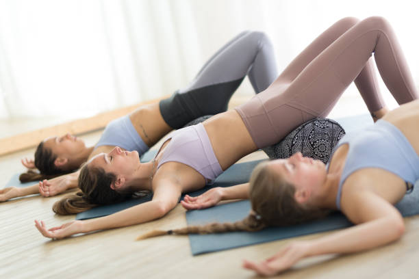 Restaurativeyoga mit einer Stütze. Gruppe von drei jungen sportlichen attraktiven Frauen im Yoga-Studio, liegend auf Bolsterkissen, Dehnen und Entspannen beim erholsamen Yoga. Gesunder aktiver Lebensstil – Foto