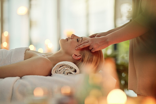 Cropped shot of a young woman enjoying a head massage at a spa
