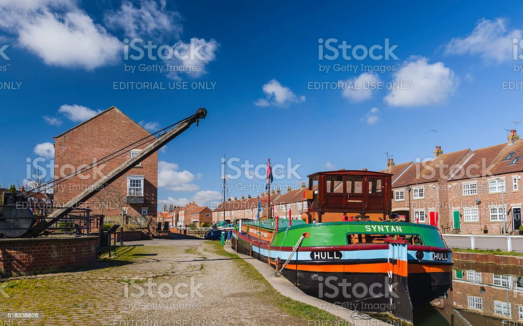 Restored barges, old winch, and town houses, along the beck. stock photo