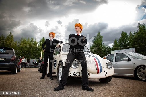 Moscow, Russia: July 06, 2019: Restored Volkswagen beetle stylized number 53. The Weasley Brothers are standing nearby. Cosplay on the theme of retro and films.