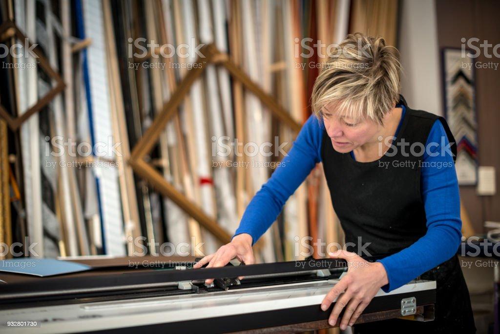 Restorer and framer laboratory craftswomen: Cutting frames stock photo