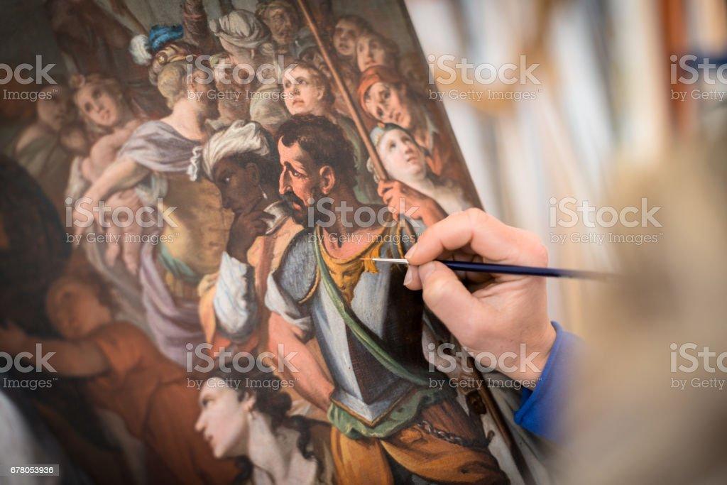 Restorer and framer laboratory craftswomen: Restoring antique religious painting canvas stock photo