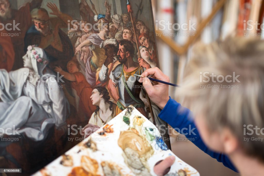 Restorer and framer laboratory craftswomen: Restoring antique religious painting canvas stock photo