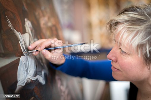 istock Restorer and framer laboratory craftswomen: Restoring antique religious painting canvas 678065772