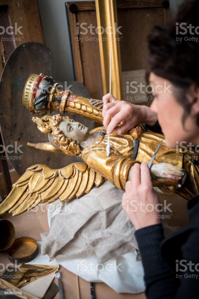 Restorer and framer laboratory craftswomen: Restoring antique golden angel statue stock photo