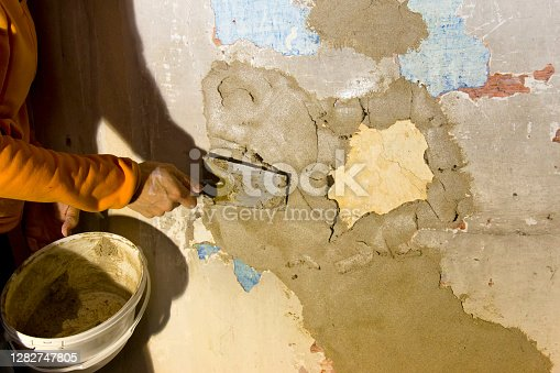 Restorer with plastering tools and fresh plaster restoring an old interior wall of a 300 years old historic farmhouse. The old wall paintings, which are over 300 years old, is to be largely preserved.